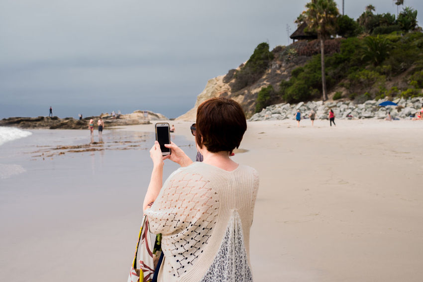 Woman talking a photograph of the ocean and beach Beach Beauty In Nature Cellphone Photography Coastline Enjoyment Focus On Foreground Incidental People Leisure Activity Lifestyles Non-urban Scene Person Phone Camera Photography Rear View Relaxation Scenics Sea Shore Sky Tourism Tourist Tranquil Scene Tranquility Vacations Water