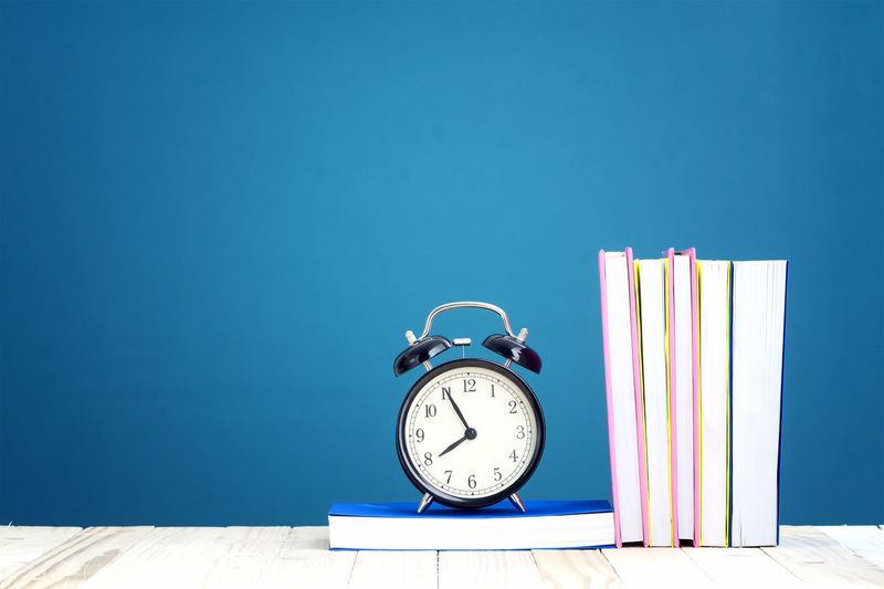 Education Concept. Text Books and alarm clock on the wooden pallet table with copyspace Books Examination Student Alarm Clock Backgrounds Blackboard  Clock Copy Space Day Desk Organizer Education Indoors  Knowledge No People Pallet School Studio Shot Studying Supplies Table Time