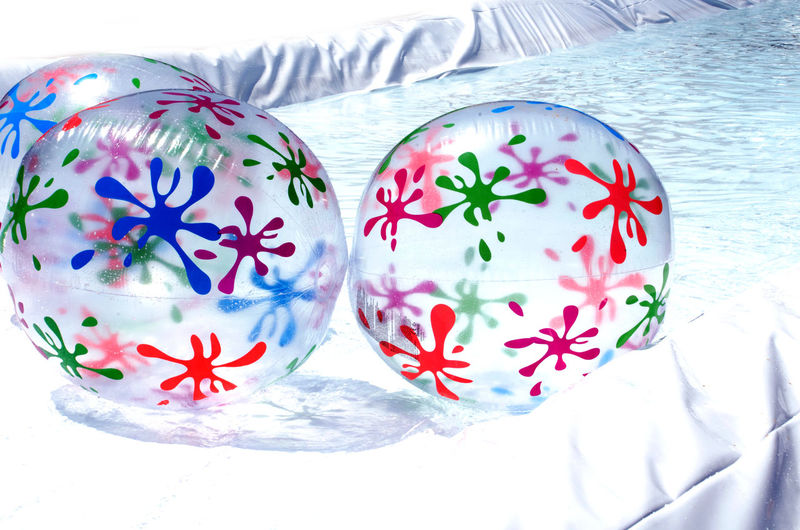 inflatable beach balls float in a pool Blow Up Fun In The Sun Inflatables In Swimming Pool Summertime Toys Ball Celebration Childhood Close-up Colorful Day No People Play Pool Toys Reflection Seaonal Shiny Summer Summer Toys Transparent Water
