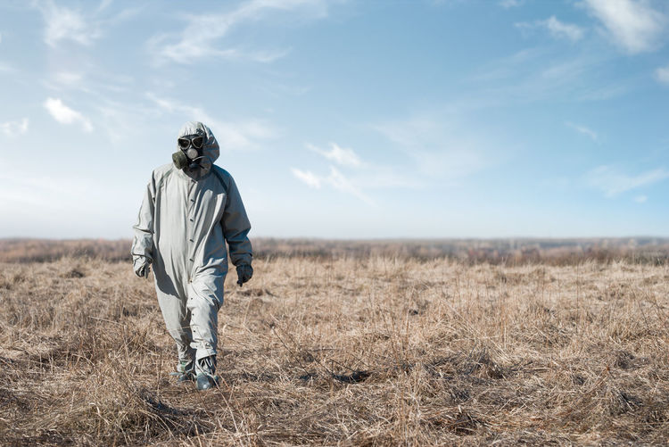 Man in gas mask and costume walking against sky