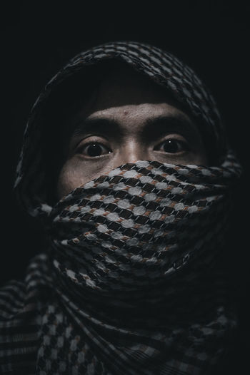 Close-up portrait of man covering face against black background