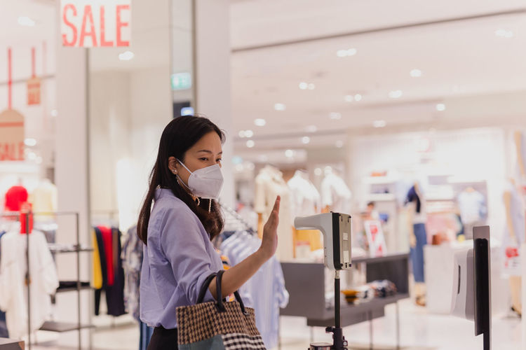 Woman looking at camera while standing against store