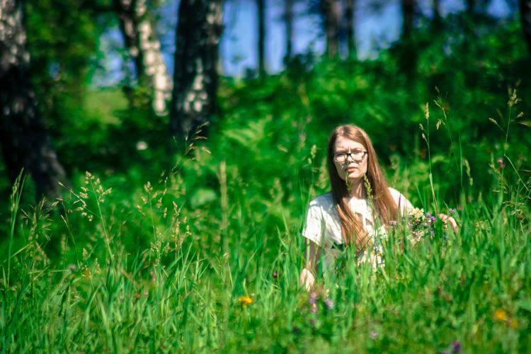 Woman sitting on grassy field