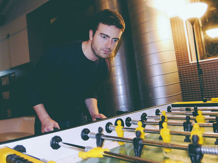 Handsome man playing foosball at club