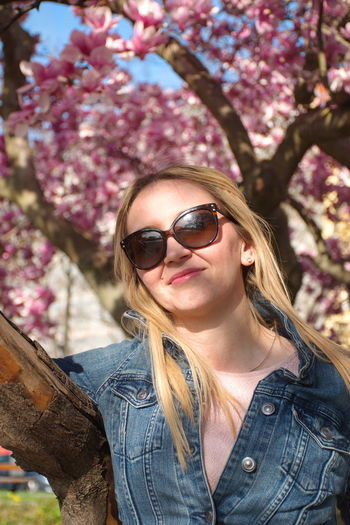 Sunglasses Tree Glasses One Person Plant Young Adult Front View Hairstyle Long Hair Portrait Hair Fashion Leisure Activity Flower Young Women Lifestyles Real People Casual Clothing Flowering Plant Outdoors Springtime Beautiful Woman Jeans Magnolia Blooming Park Pink Color