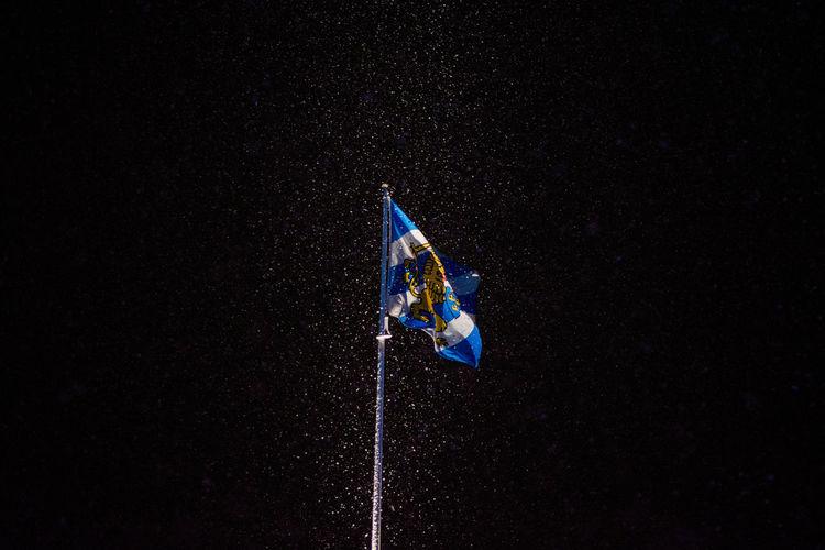 Blue flag waving against black background
