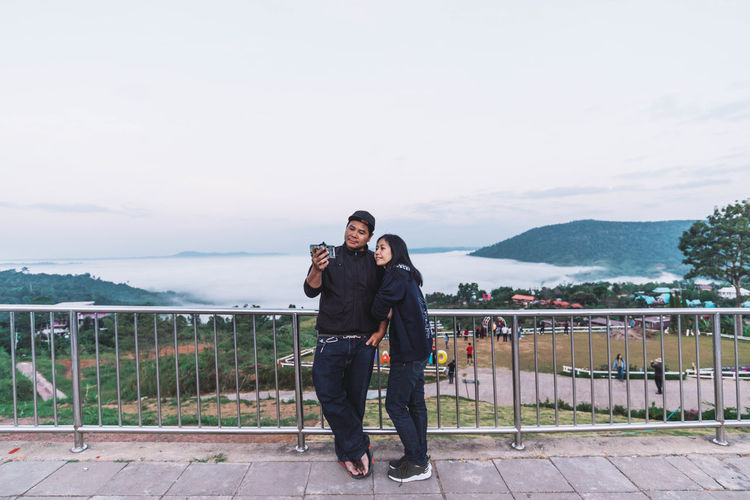 Full length of couple standing with mobile phone by railing against sky