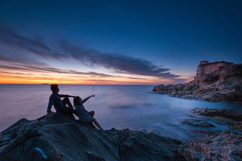 Couple sitting on rock formation by sea against sky during sunset