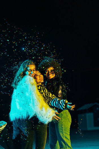 Young smiling women throwing confetti on stage