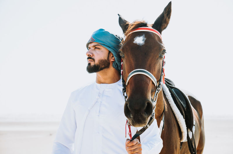 Portrait of young man with horse against white background