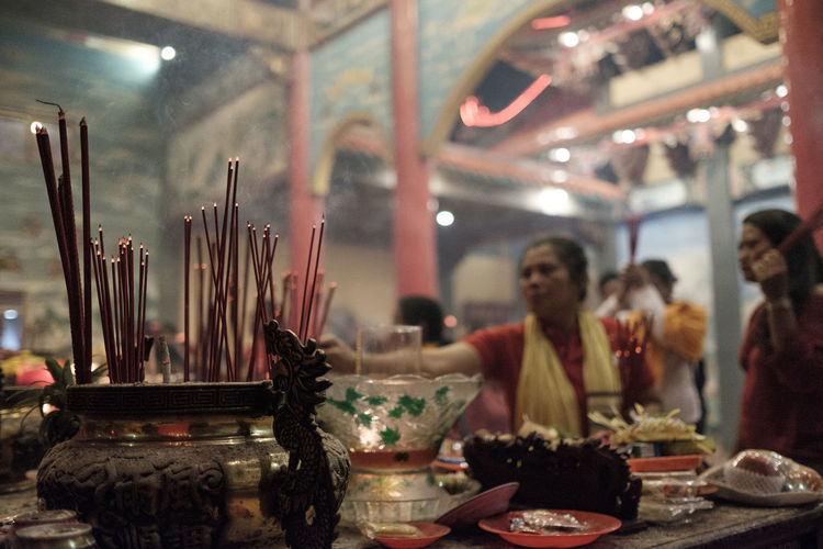Benoa, Bali, Indonesia - January 28, 2017 : People praying and wishing a happy chinese new year on vihara satya dharma. Belief Built Structure Business Candle Focus On Foreground Food And Drink Group Of People Illuminated Incense Incidental People Indoors  Place Of Worship Real People Religion Spirituality Table Women