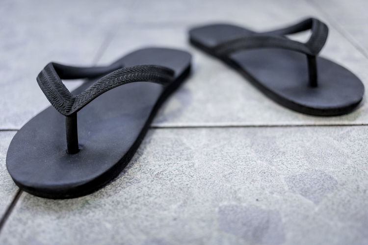 High angle view of black flip flops on footpath