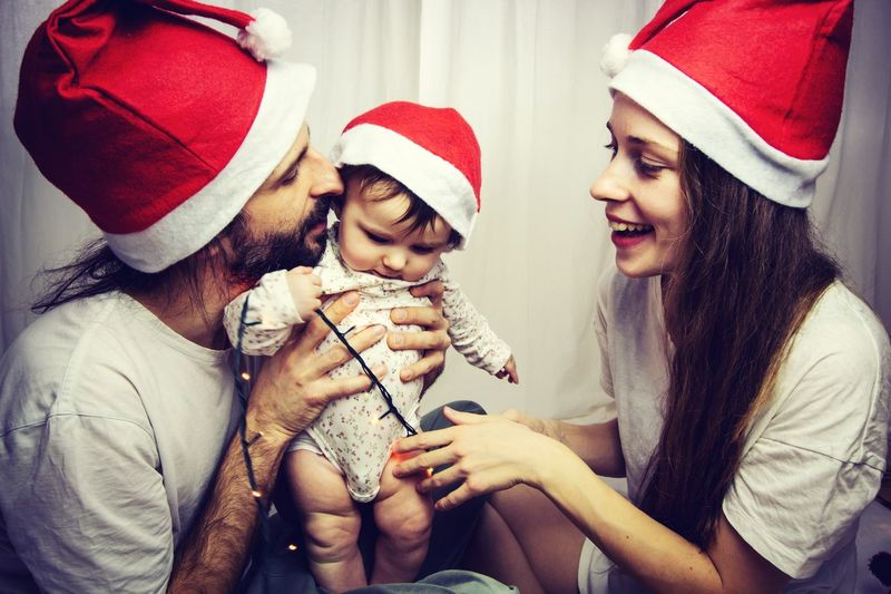 young family with santa hats having fun at christmas time Christmas Spirit Christmastime Family Christmas Is Coming Xmas Baby EyeEm Selects Hat Celebration Clothing Santa Hat Real People Togetherness Christmas Smiling Happiness Winter Positive Emotion Holiday Moments Moments Of Happiness