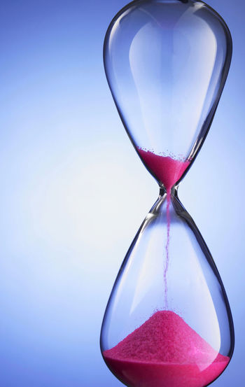 Hourglass on blue background Antique Countdown Deadline Flowing Isolated Past Retro Running Blue Background Clock Close-up Glass Hour Glass Hourglass Indoors  Instrument Measurement No People Old Passing Sand Single Object Still Life Time Timer