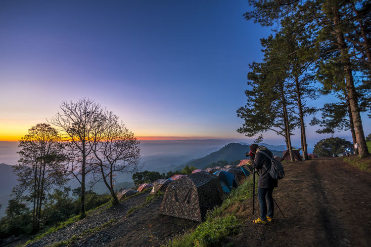 twilight and photographer on monson viewpoint at doi angkhang mountain of chiangmai in Thailand ASIA Camera Camping Cloud Light Morning Thailand Tourist Travel Tree Twilight Winter Wood Fog Forest Landscape Lifestyles Mountain Nature Outdoors Photographer Sky Sunset Tent Tree The Traveler - 2018 EyeEm Awards