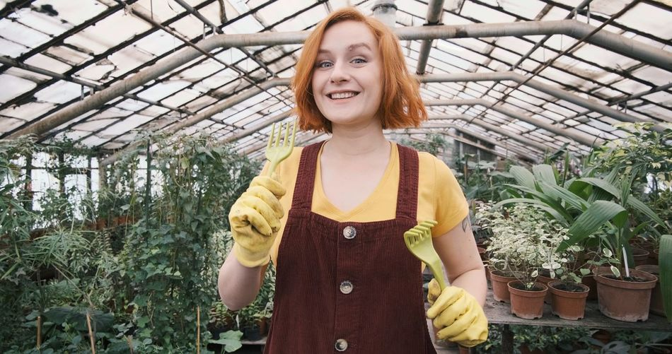 Portrait of smiling young woman standing in greenhouse