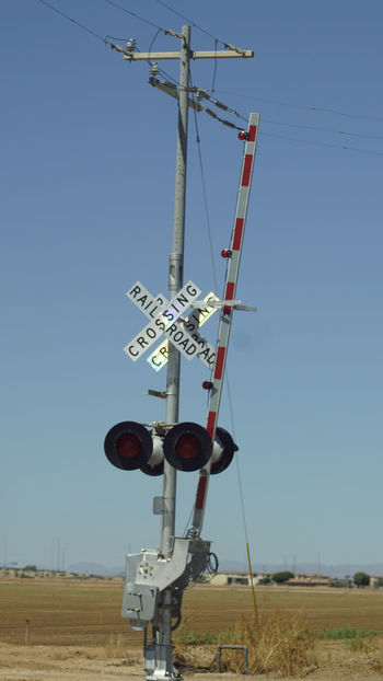 Blue Clear Sky Communication Crossing Sign Day Field Guidance Landscape Low Angle View Nature No People Outdoors Rail Transportation Railway Signal Sky Transportation