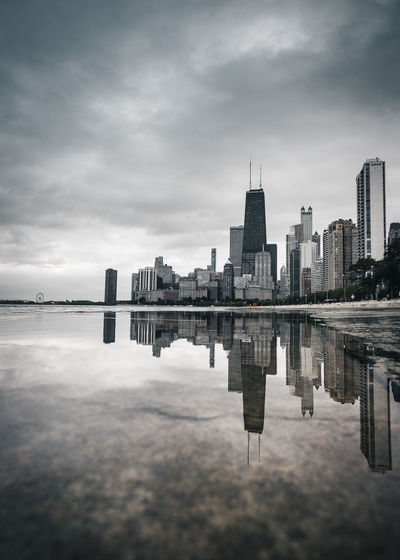 Reflection of modern buildings in river against cloudy sky