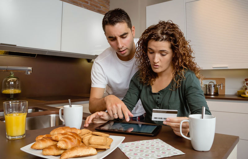 Portrait of young couple with electronic tablet reviewing credit card monthly payouts. Electronic bank concept. Serious Upset Budget Worried Money Two Family Paying Wireless Commerce Female Male Caucasian Ecommerce E-commerce Buying People Coffee Cup Breakfast Lifestyle Payment Shopping Internet Home Kitchen Wife Woman Man Review Bankruptcy Desperate Unhappy Crisis Recession Insolvency Economy Financial Bill Finance Debt Problem Couple Online  Credit Card Card Credit Pad Electronic Tablet