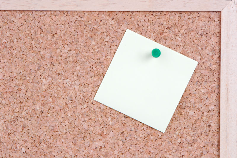 Close-up of white paper on bulletin board