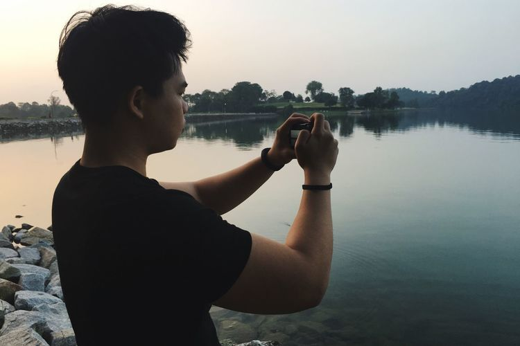 Young man in lake against sky