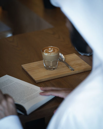 Coffee on Wooden Table with Book in Cafe Ijas Muhammed Photography Drink Real People Table Food And Drink Human Hand Refreshment Hand Holding One Person Human Body Part Indoors  Publication Men Book Selective Focus Coffee - Drink Paper Adult Coffee Glass