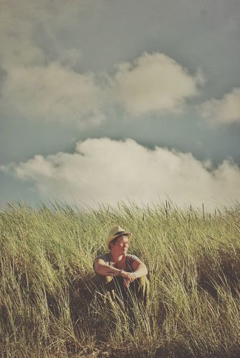 Man sitting on grassy field against sky