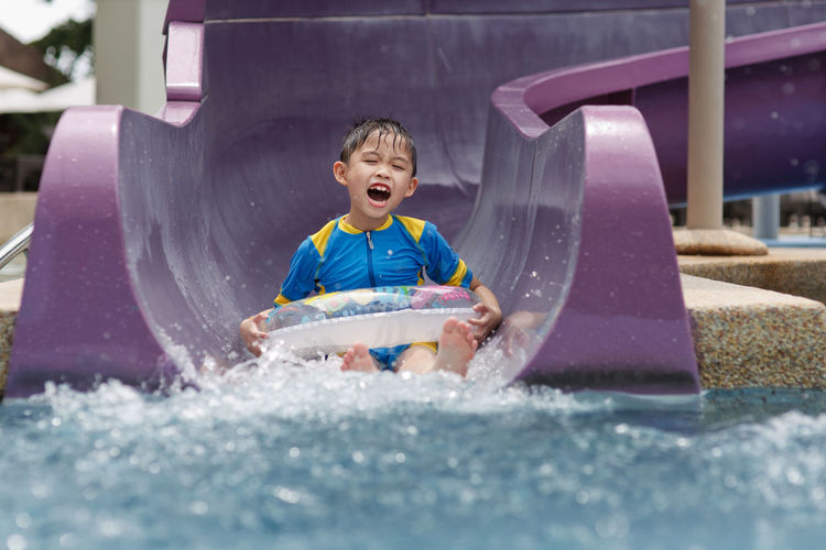 Boy sliding down in water slide at water park