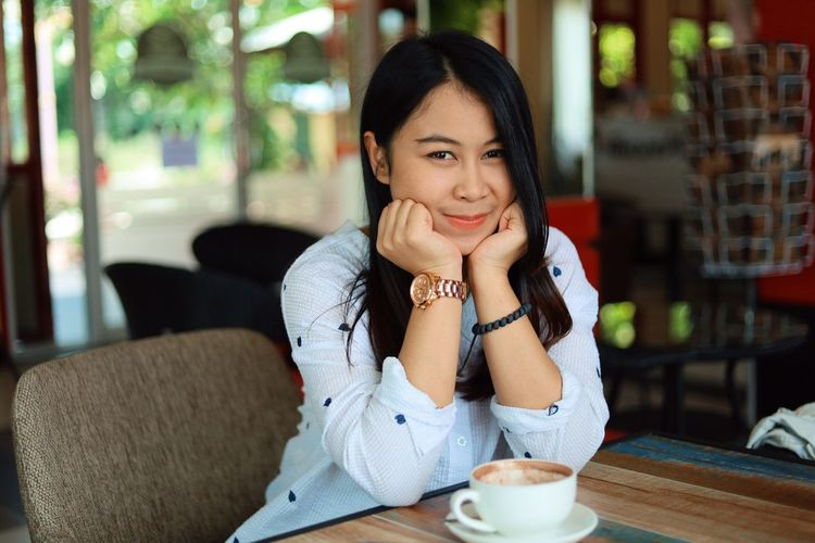 Sitting Food And Drink One Person Drink Smiling Cup Table Front View Portrait Women Coffee - Drink Young Adult Adult Cafe Restaurant Casual Clothing Coffee Looking At Camera Refreshment Hair Hairstyle Hot Drink Saucer Beautiful Woman Drinking