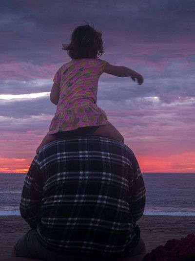 Rear view of father carrying daughter on shoulders at beach during sunset