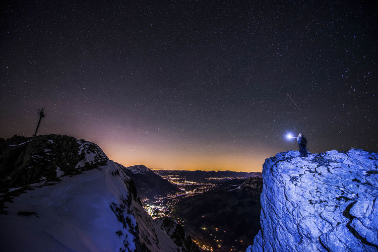 Person Standing On Snowcapped Mountain Against Sky At Night