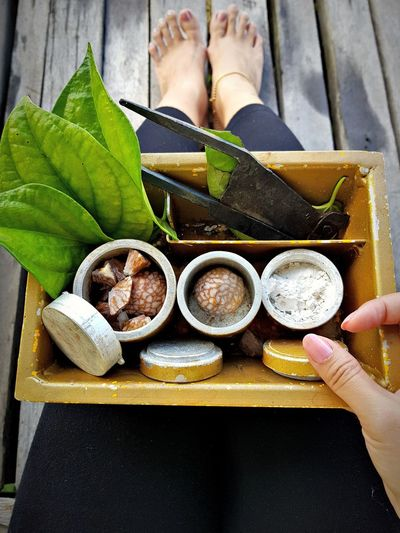 High angle view of woman preparing paan on boardwalk