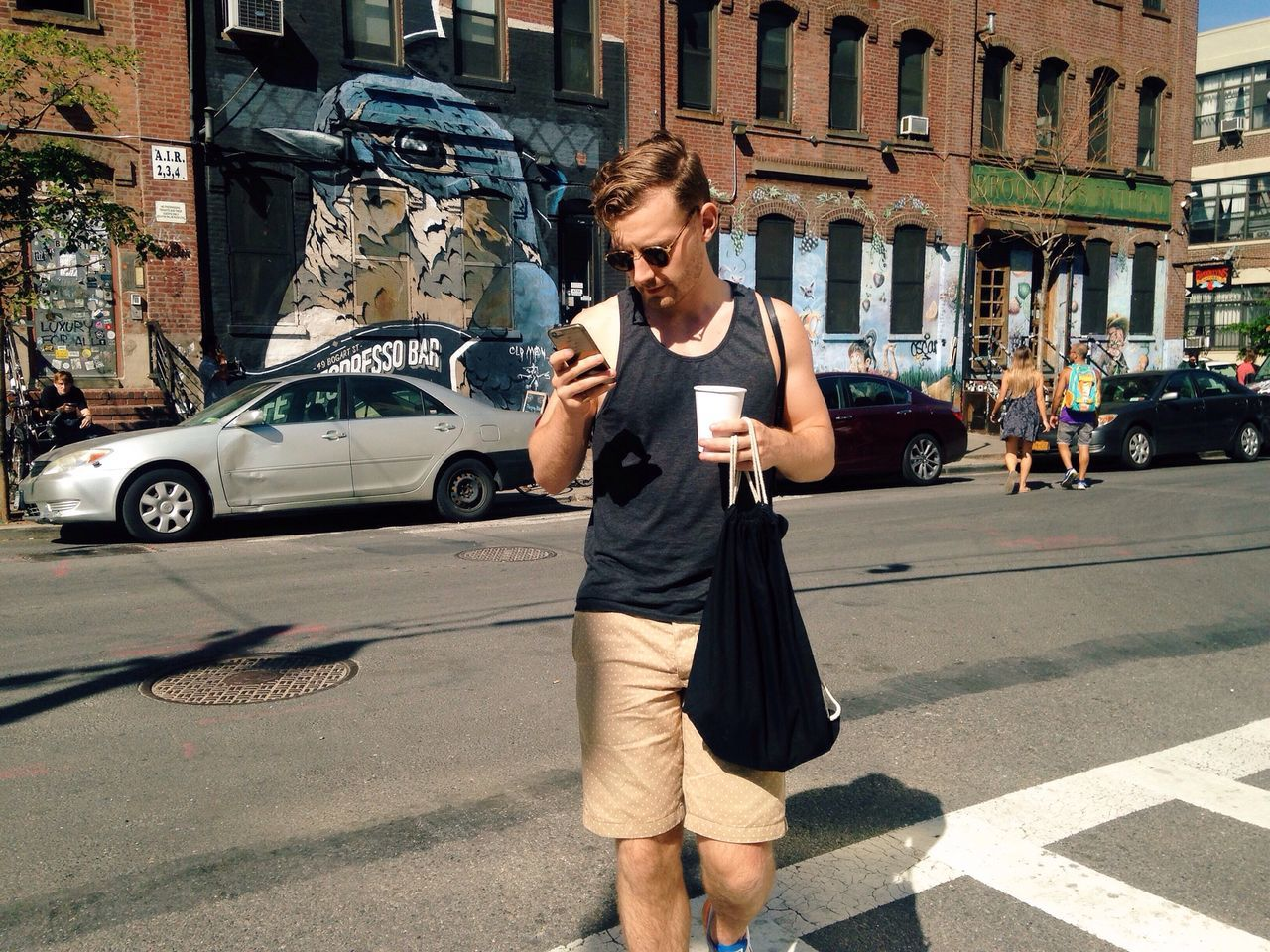 Young man using smart phone while carrying bag and coffee cup on street