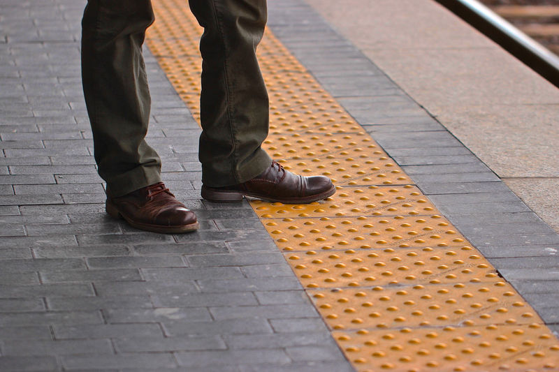 Low section of man standing on railroad station platform