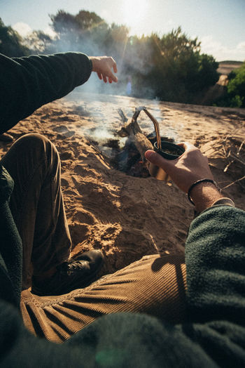 Low section of man holding smoking pipe while camping outdoors