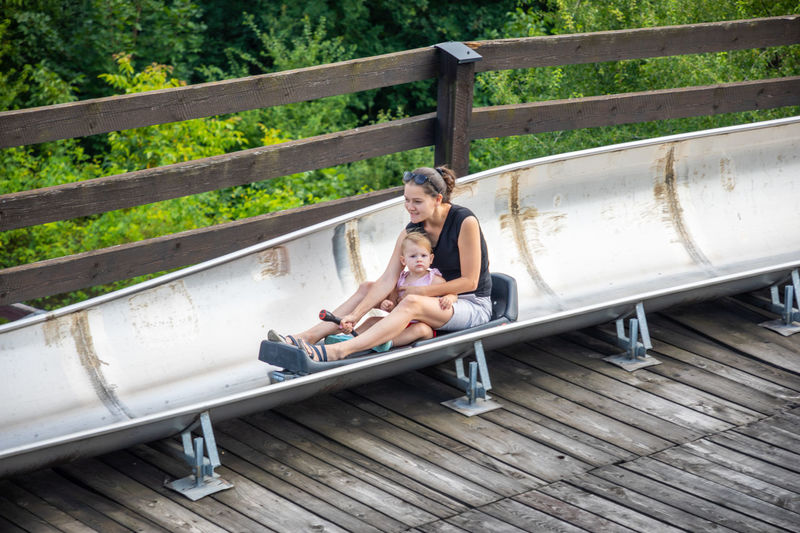 Side view of woman sitting on railing