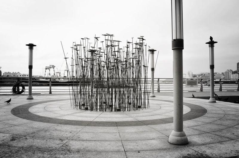 Fishing poles on pier against sky