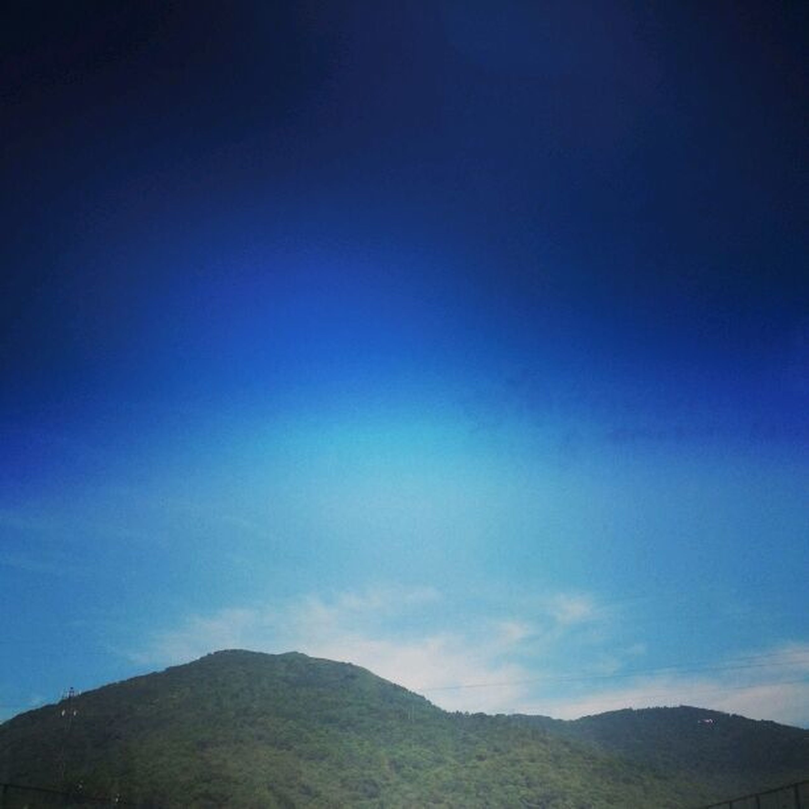 blue, mountain, tranquil scene, tranquility, scenics, beauty in nature, sky, mountain range, landscape, nature, copy space, idyllic, non-urban scene, low angle view, outdoors, remote, day, no people, cloud, cloud - sky