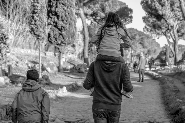Rear View Of Family Walking At Park