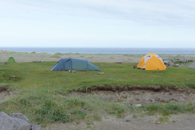 Tent on field by sea against sky