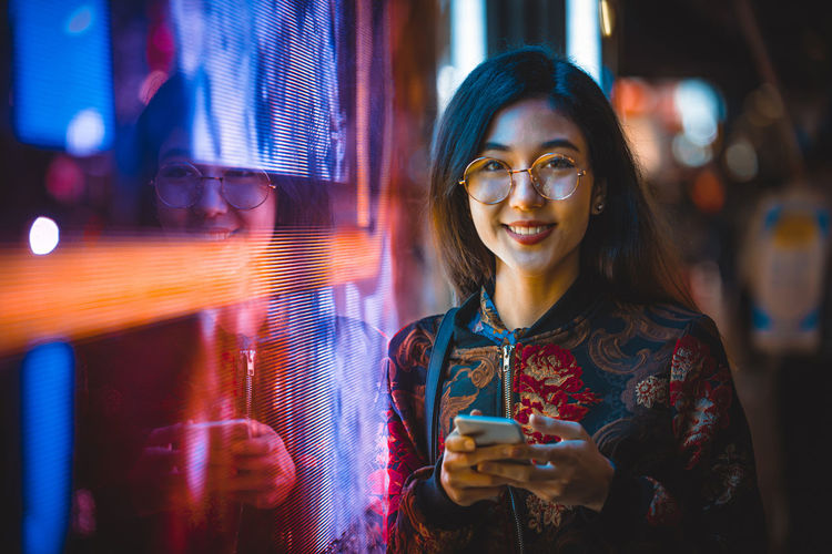 Portrait of smiling young woman using smart phone by window with reflection at night