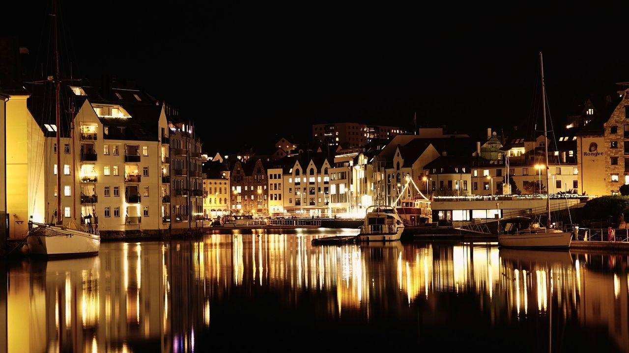 SAILBOATS MOORED IN RIVER AGAINST BUILDINGS AT NIGHT