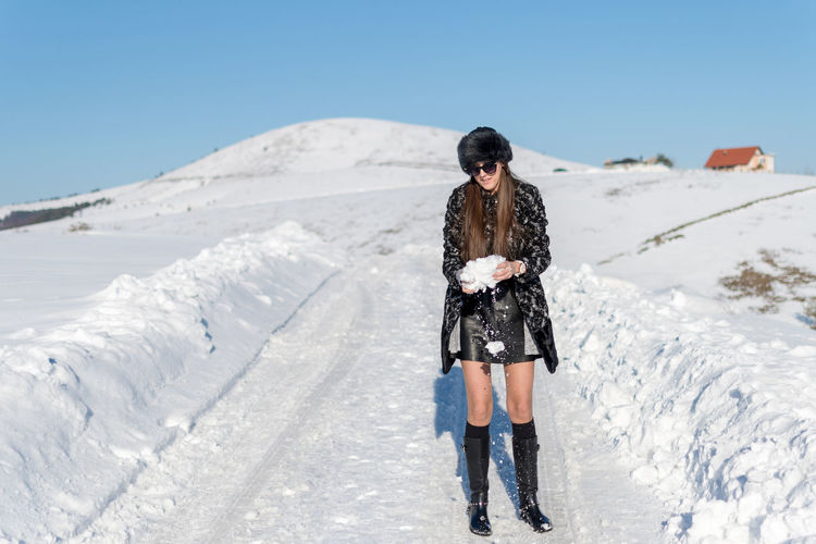 One Person Lifestyles Leisure Activity Real People Snow Front View Young Adult Cold Temperature Standing Day Full Length Beauty In Nature Nature Winter Scenics - Nature Sky Clothing Clear Sky Warm Clothing Outdoors Extreme Weather