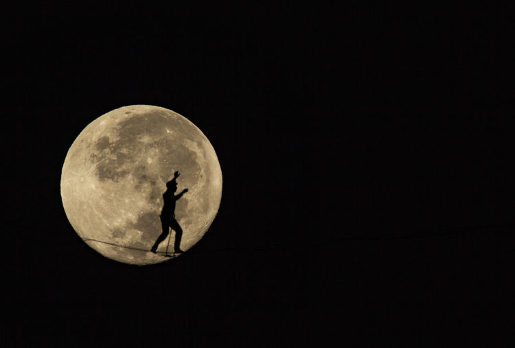 Silhouette man against moon in sky