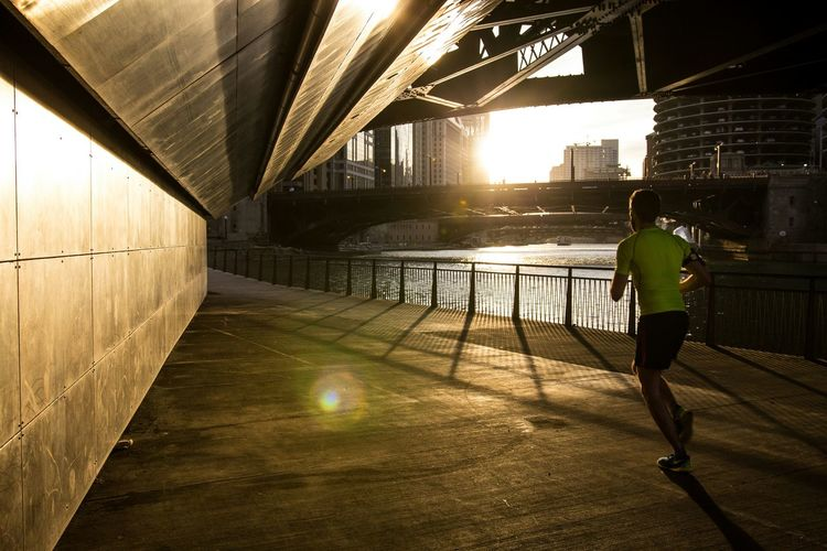 Full Length Rear View Of Man Running On Bridge During Sunny Day