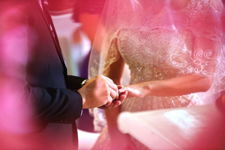 Midsection Of Bridegroom Sliding Ring On Bride Finger During Wedding Ceremony