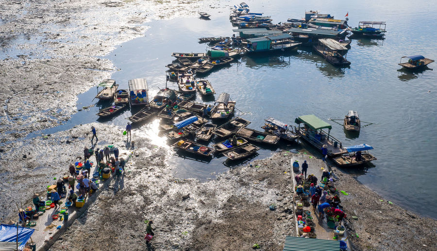 High angle view of people by boats on sea