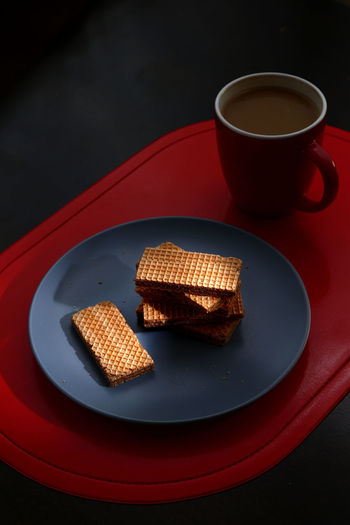 chocolate wafers on a plate and a mug of coffee Sweet Sweet Food Sweets Dessert Chocolate Wafer Food Snack Time! Snacks! Meal Coffee Coffee - Drink Drink Beverage Wafer Chocolate Crispy Drink Plate Studio Shot Red Close-up Food And Drink Sweet Food Coffee Cup