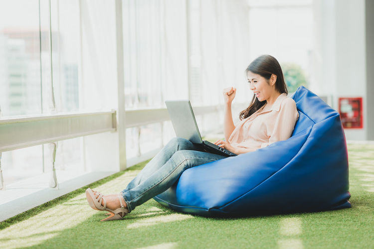 Businesswoman using laptop while sitting on bean bag on office