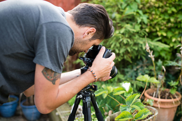 Man Photographing Potted Plant